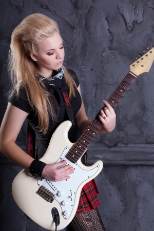 teenager rockstar with electric guitar against wall background Stock Photo - 17229245