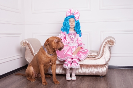 Cute girl dressed like Malvina with dog posing on sofa photo