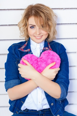 Beautiful young woman with heart shaped pink pillow Stock Photo - 17356652