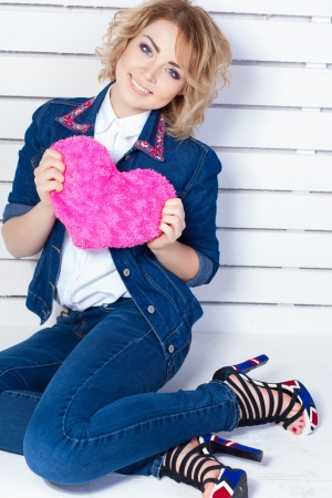 Beautiful young woman with heart shaped pink pillow Stock Photo - 17356653