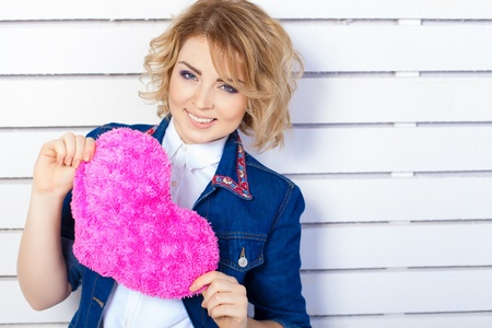 Beautiful young woman with heart shaped pink pillow Stock Photo - 17356651