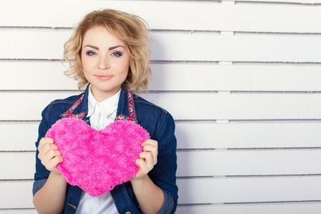 Beautiful young woman with heart shaped pink pillow Stock Photo - 17356648