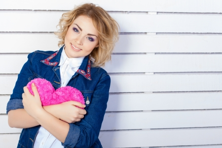 Beautiful young woman with heart shaped pink pillow Stock Photo - 17356650