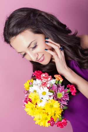 Elegant fashionable woman with flowers over pink background Stock Photo - 17342050
