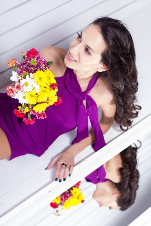 Elegant fashionable woman with flowers over wall background Stock Photo - 17342053