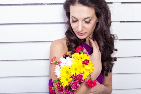 Elegant fashionable woman with flowers over wall background Stock Photo - 17342052