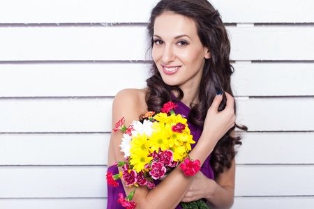 Elegant fashionable woman with flowers over wall background Stock Photo - 17342046