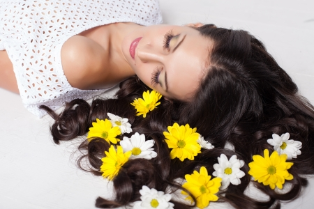 beautiful young woman lying with flowers in long hair photo