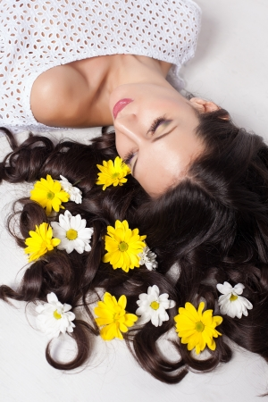 beautiful young woman lying with flowers in long hair Stock Photo - 17342045