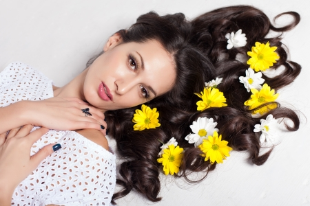 beautiful young woman lying with flowers in long hair Stock Photo - 17342055