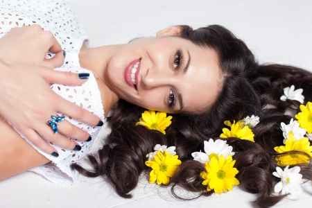 beautiful young woman lying with flowers in long hair Stock Photo - 17342047