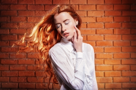 Portrait of fashionable woman with long red hair in motion over wall backgroun Stock Photo - 17342049