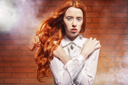 Portrait of fashionable woman with long red hair in motion over wall backgroun Stock Photo - 17342051