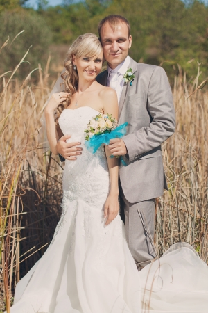 Happy young bride and groom kissing in grass in wedding day Stock Photo - 17416188