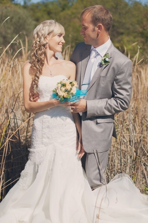 Happy young bride and groom hugging in grass on their wedding day Stock Photo - 17416198