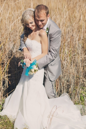 Happy young bride and groom hugging in grass on their wedding day Stock Photo - 17416221
