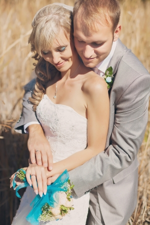Happy young bride and groom kissing in grass in wedding day Stock Photo - 17416197