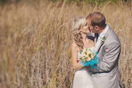 Happy young bride and groom kissing in grass on their wedding day photo