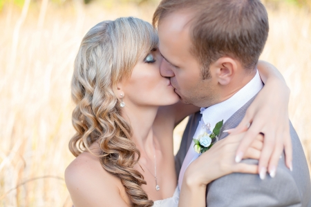 Happy young bride and groom kissing in grass on their wedding day Stock Photo - 17416208