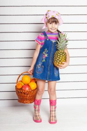 girl with basket of fruits over wall background Stock Photo - 17416191