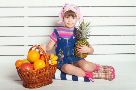 girl with basket of fruits over wall background Stock Photo - 17416192