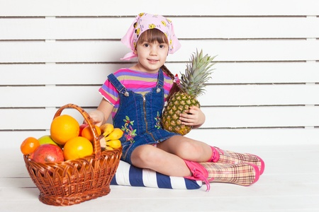 girl with basket of fruits over wall background photo