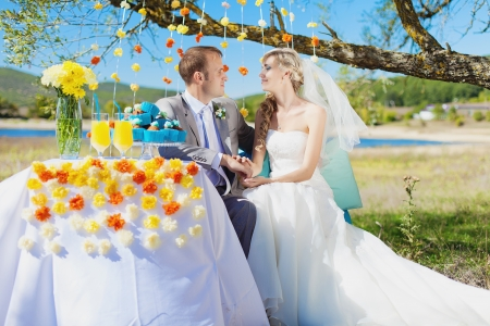 couple bride and groom at wedding decorated table in park photo