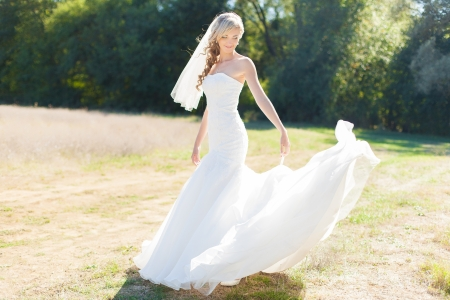 Portrait of beautiful blond bride in action  Wedding dress Stock Photo - 17416228