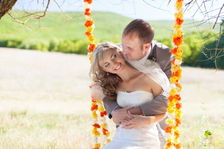 couple in love bride and groom on swing in park in their wedding day Stock Photo - 17405786