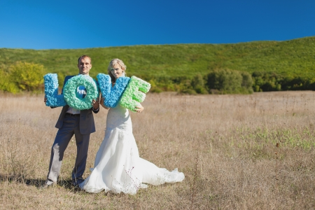wedding  bride and groom holding letters of word LOVE photo