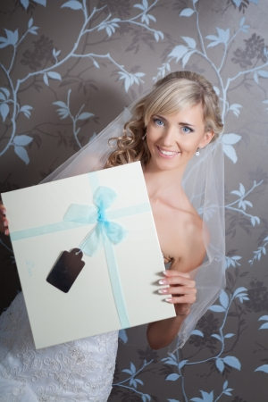 Beautiful blond bride portrait in white dress with gift box Stock Photo - 17480217