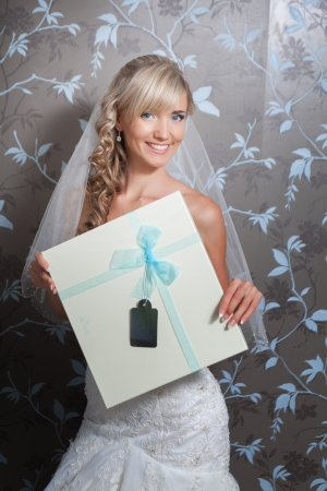 Beautiful blond bride portrait in white dress with gift box Stock Photo - 17480216