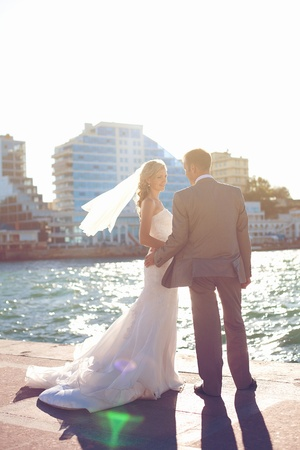 wedding  couple in love bride and groom posing on waterfront in the urban landscape photo