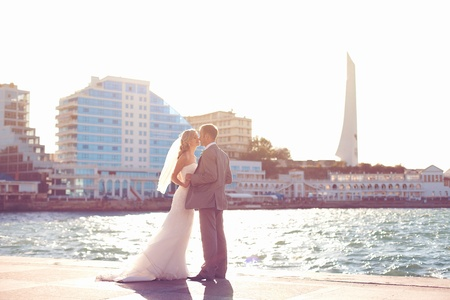 wedding  couple in love bride and groom posing on waterfront in the urban landscape Stock Photo - 17480218