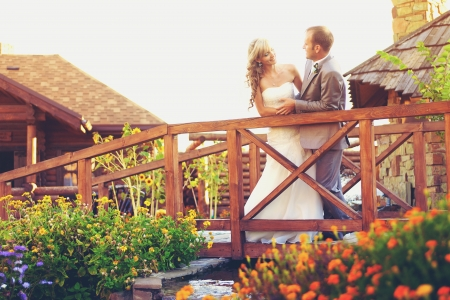 wedding  couple in love bride and groom in garden posing on a wooden bridge