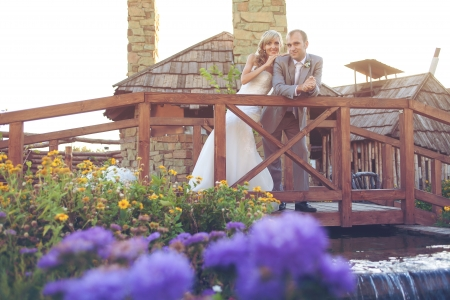 wedding  couple in love bride and groom in garden posing on a wooden bridge  photo
