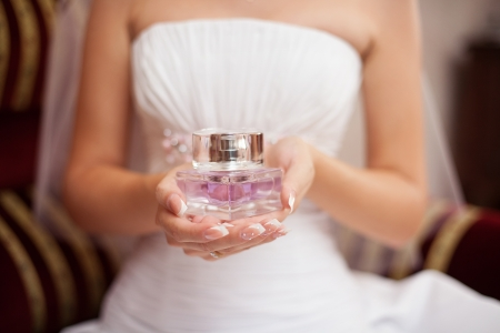 bride in white wedding dress with perfume bottle Stock Photo