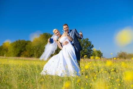 wedding couple hugging on chamomile meadow photo