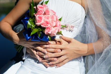 hands of the groom hugging bride with wedding bouquet of roses photo