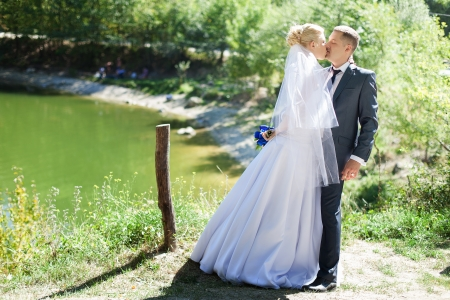 wedding couple in love bride and groom over lake background photo