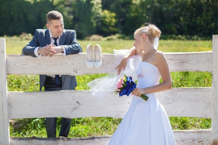 beautiful bride and groom on farm near wooden fence photo