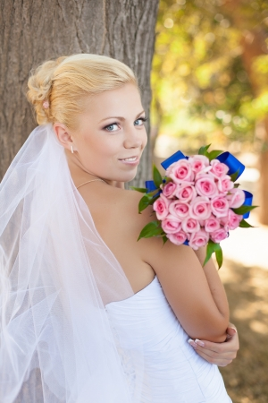 Portrait of the bride with wedding bouquet over tree background