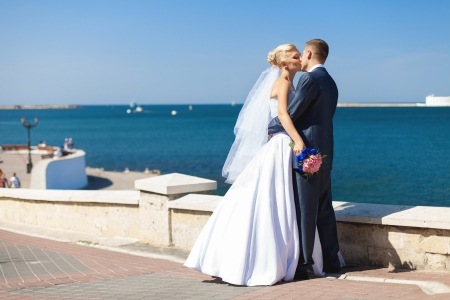 couple in love bride and groom posing on waterfront in their wedding day photo