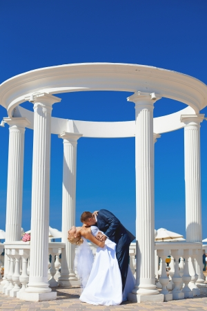 Young couple in love bride and groom posing with white columns on the background of bright blue sky  Wedding day in summer photo