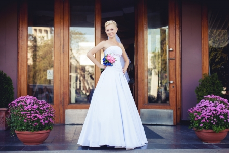 bride standing at the door of hotel in her wedding day photo