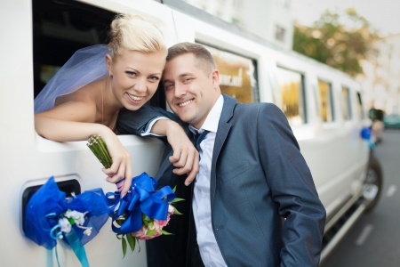 wedding reception: couple in love bride and groom posing at car window