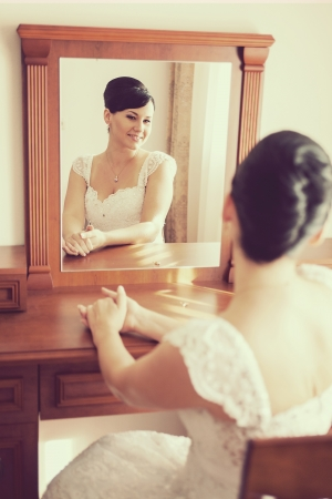 wedding  Happy beautiful brunette bride sitting on chair and looking through mirror photo