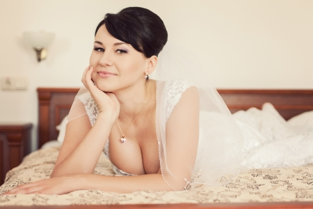 Portrait of happy beautiful brunette bride lying on bed in wedding day photo