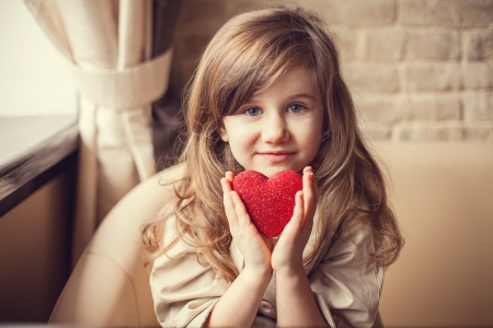 family and health: Valentine Day - dreaming cute child with red Heart in hands.
