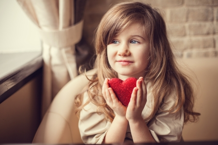 preschoolers: Valentine Day - dreaming cute child with red Heart in hands.